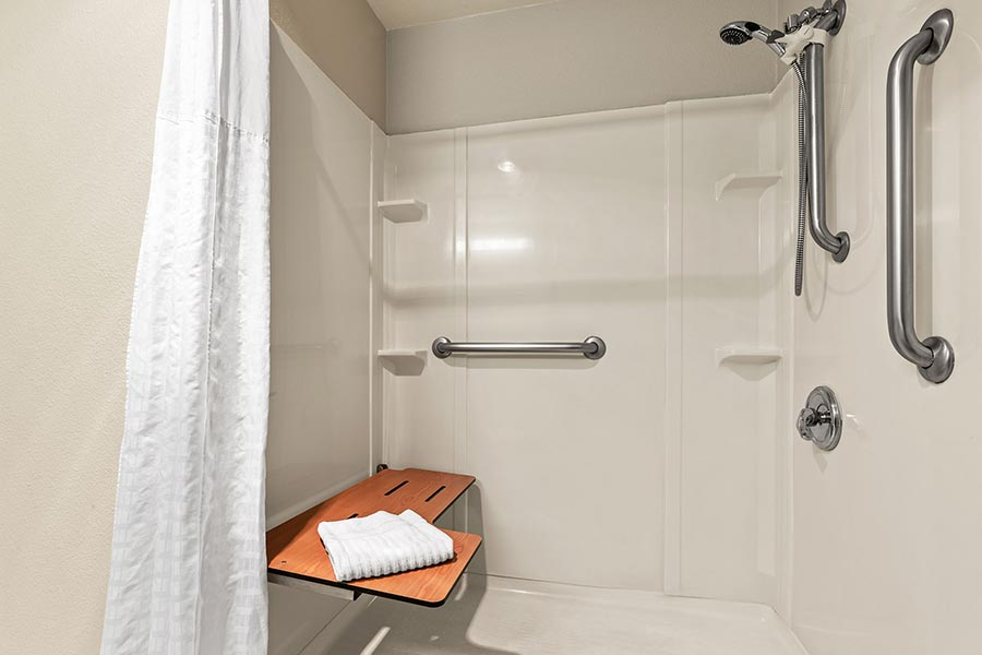 accessible roll-in shower with seat and grab bars